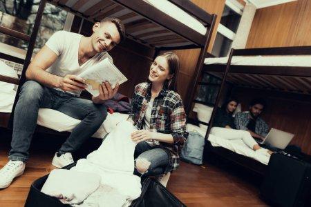 Photo pour Auberge pour les jeunes. Meilleurs amis voyageant. Petite chambre en auberge. passer du temps ensemble. lits superposés dans la chambre. Les gens souriants.. assis sur le lit. déballer le sac. tenant la carte. regarder sur la carte ensemble - image libre de droit