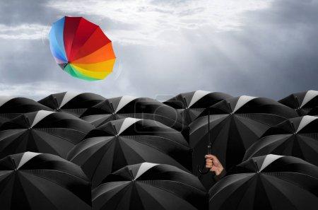 Umbrella in mass of black umbrellas.