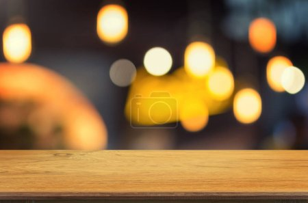 Empty wooden table and blurred Coffee shop interior background with bokeh image, for product display montage,can be used for montage or display your products