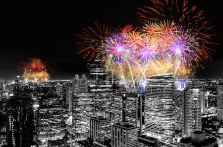 Fireworks celebrating over cityscape at night of Thailand.