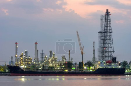 Photo for Oil Refinery Industry at night Construction more A cargo ship moored on the river front. - Royalty Free Image