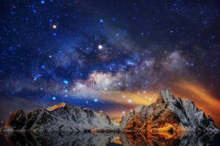Milky Way over Mountain landscape, Reine village in Lofoten islands of Norway.