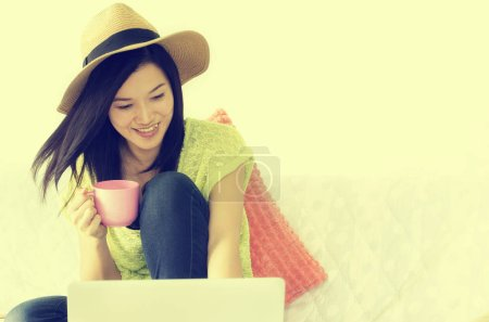 Photo for Happy young woman using laptop and holding pink cup of coffee indoor. Vintage Style. - Royalty Free Image