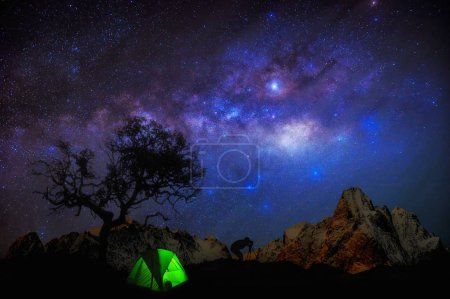 Milky Way with stars and tent in foreground, Traveler camping on mountain.