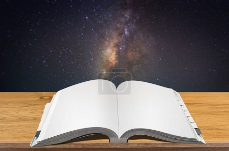 Open book on wooden table with blurred Milky way background.