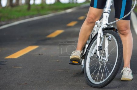 Photo for Below body of young woman with her bicycle. - Royalty Free Image