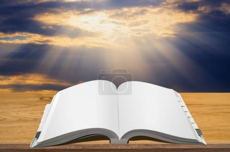 Open book on wooden table with sunbeams through clouds background.