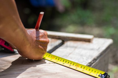 Carpenter hand measuring tape with pencil in workplace.