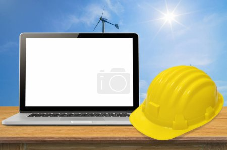 Yellow safety helmet and laptop on desk with industry background, blank on screen.