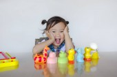 Happy cute asian little kid sitting at table and playing with colorful toy.