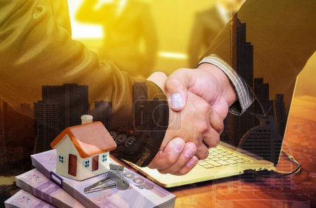 Handshake  with real estate agents, house models on banknotes and keys. The concept of home trading agreement.