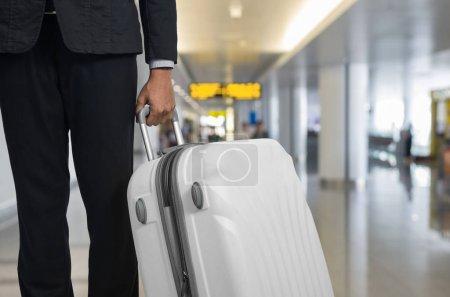 Photo pour Homme d'affaires et valise dans le salon de départ de l'aéroport, avion en arrière-plan flou, concept de vacances d'été, valises de voyageur dans la zone d'attente du terminal de l'aéroport . . - image libre de droit