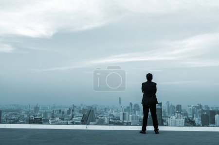 Photo for Businessman standing on top of building and viewing modern city. - Royalty Free Image