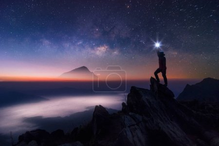 Silhouette of climber or backpacker. In his hand, he held the light up high above his head. Standing on rocky mountain peak and Milky Way Galaxy, success, winner, leader concept. High iso with Noise.