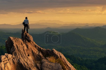 Photo for Concept vision, Young businessman wearing comfortable casual suit jacket standing holding business bag on top of peak mountain and looking forwards, success, competition and leader concept. - Royalty Free Image