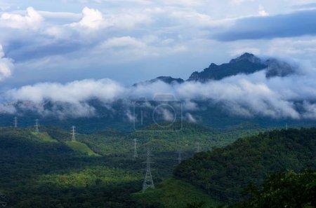 Photo pour Tours de transmission d'énergie haute tension avec brouillard sur la montagne mae moh lampang . - image libre de droit