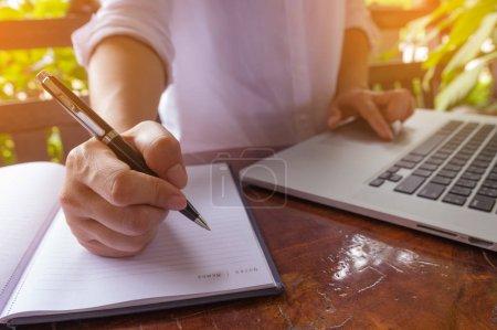Foto de Bolígrafo de mano en el portátil y las manos de la mujer independiente en el ordenador portátil del teclado en un café, niña usando escritura portátil, búsqueda web, navegación / imagen de enfoque suave . - Imagen libre de derechos
