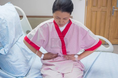 Woman patient with stomach pain at room in the hospital.