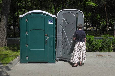 Photo for Portable toilets, the woman enters the toilet on the right, on the left only for the disabled ... - Royalty Free Image
