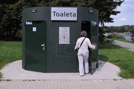 Photo pour Toilettes automatiques, installation publique dans le parc, femme entre dans les toilettes précédemment payées, entrée pour handicapés sur la gauche  ... - image libre de droit