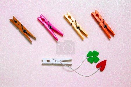 Photo pour Ensemble coloré de cinq pinces à linge en bois et en plastique sur un fond scintillant rose clair avec de l'espace. Un cœur rouge et une feuille de trèfle vert chanceux sont attachés à la pince en bois blanc. Vue de dessus . - image libre de droit
