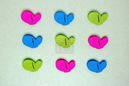 Photo pour Ensemble coloré de neuf pinces à linge ou chevilles en plastique sur fond vert clair scintillant avec champ de copie. Vue d'en haut. - image libre de droit