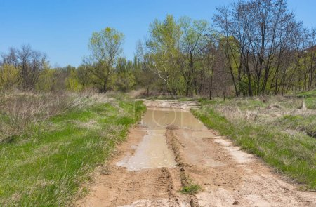 Spring landscape with clay dirty road in rural Ukrainian area
