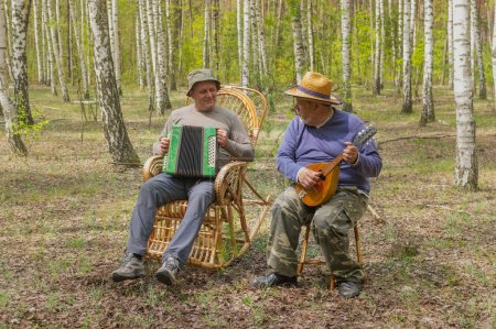 Photo pour Deux personnes âgées vont jouer de la musique dans la forêt de bouleaux - image libre de droit
