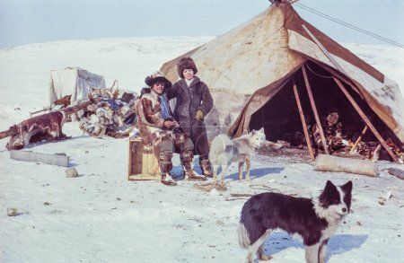 Chukchi Peninsula, USSR - May 5, 1983: Caucasian woman poses with Chukchi man while visiting remote station of the indigenous people in tundra