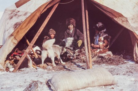 Chukchi Peninsula, USSR - May 1983: Caucasian woman having conversation with family of the indigenous people inside of their yaranga (tent)