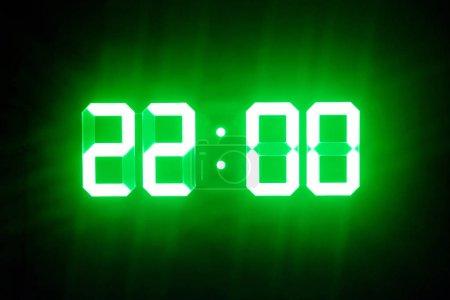 Les horloges numériques lumineuses vertes dans l'obscurité montrent 22 : 00 heure