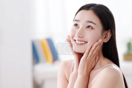 Photo for Beautiful young woman applying cosmetic cream - Royalty Free Image