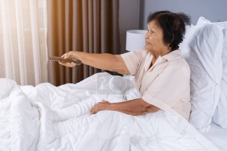 Happy senior woman in bed with remote control and ...