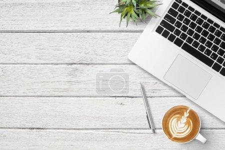 Photo pour Table de bureau en bois blanc avec ordinateur portable, tasse de café et fournitures. Vue du dessus avec espace de copie, plan plat. - image libre de droit