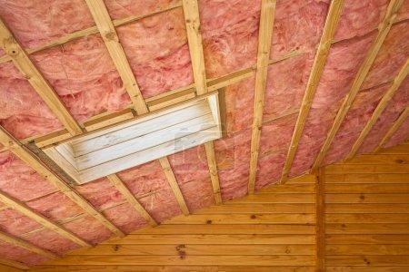 Foto de Aislamiento de fibra de vidrio instalado en el techo inclinado de una casa de madera . - Imagen libre de derechos