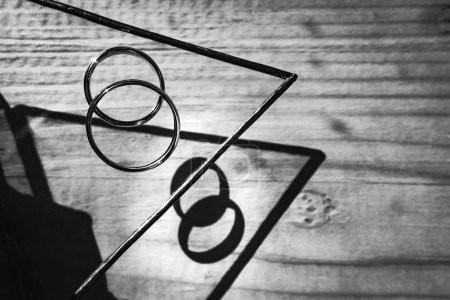 close-up photo of beautiful Wedding rings details on wooden table, black and white