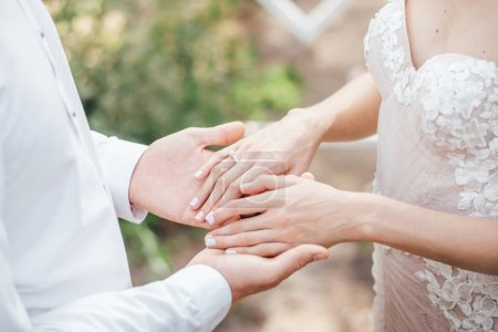 close-up photo of young couple holding hands in wedding day