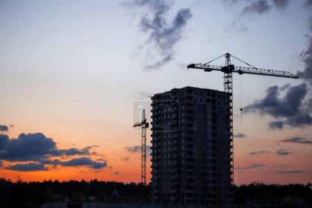 Photo for Crane and construction site against sunset. Unfinished building construction and building cranes against blue sky background. Concept of urban development. - Royalty Free Image