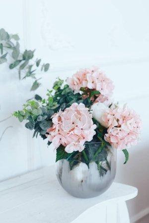 Photo pour Hortensias roses dans un vase transparent sur un tableau blanc. - image libre de droit