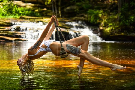 Young beautiful woman in sexy swimsuit sitting on the swing in wild forest with waterfalls on the background.