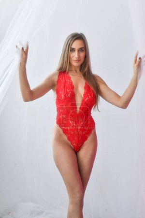 Sexy model with a perfect figure posing in red bodysuit, studio shoot.