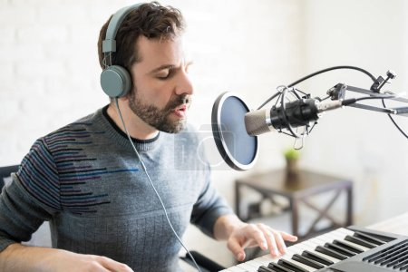 Good looking latin man singer with headphones singing a song and playing piano into mic at radio station