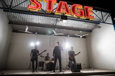 Photo for Music band playing live on stage with lights on the background - Royalty Free Image