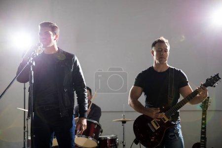 Photo pour Chanteur chante avec le guitariste jouer de la guitare électrique sur scène lors d'un concert de rock - image libre de droit