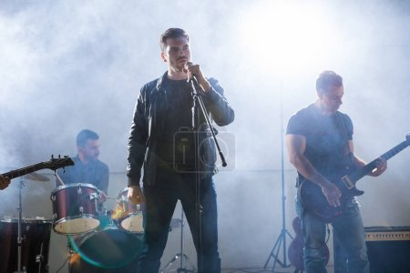 Rock band playing live on stage during a music concert with bright lights and smoke around