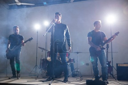 Group of four musicians playing music on stage with lights and smoke around