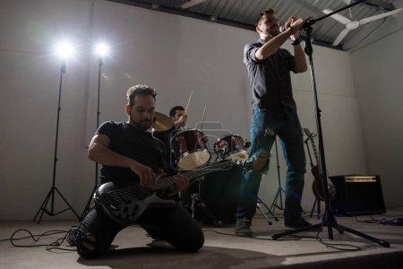 Photo pour Le guitariste joue son cœur dehors sur scène avec le chanteur et batteur à l'arrière - image libre de droit