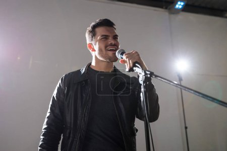 Handsome male rock singer performing on stage with microphone