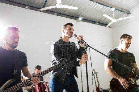 Photo pour Jeune homme chantant dans un micro avec des membres de son groupe autour de sur scène - image libre de droit