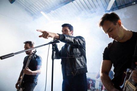 Photo pour Chanteuse avec guitaristes interprétant une chanson de rock sur la scène avec la fumée et la lumière à l'arrière - image libre de droit